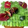 Bloemschikken: een mat weven met bladeren van gele lis en opvullen met Anthurium