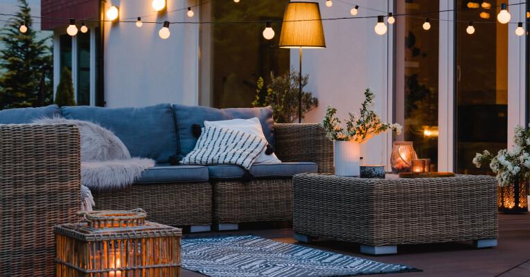 Een gezellig terras met verlichting en leuke tuinmeubelen.
